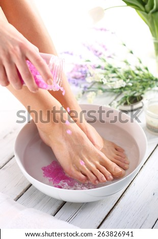Washing of feet.A woman washes the feet in a bowl of water and salt to the foot