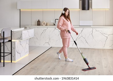 Washing floor using flat mop with microfiber pad and spray bottle, young white woman tidies up kitchen.