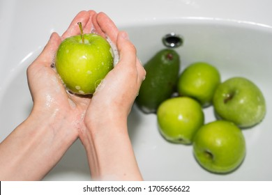 Washing fruit. Girl washes fruits and vegetables for the prevention of coronavirus covid-19 2019-ncov. Hands and soapy green apple