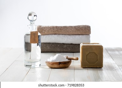 Washing green with clean anti-pollution laundry detergents made of sustainable ingredients, traditional soap, white vinegar and baking soda salt on wooden background
