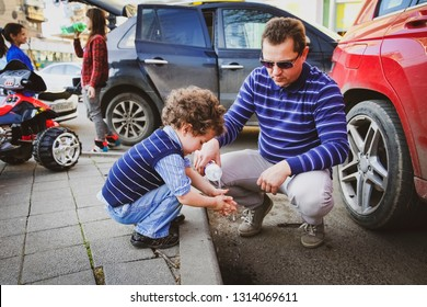 Washing Hand. Son and father on a walk, dad to pour water wash for you.