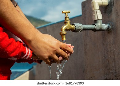 Washing hands, cleaning Baby's hands by father on the water Tap