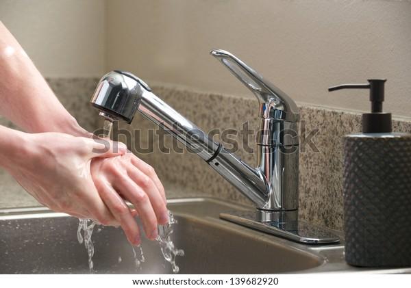 Washing hands in the kitchen sink