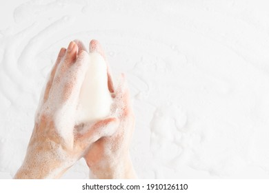 Washing of hands with soap, foam. Cleaning hands. Closeup on woman hands with foam soap bar on white background.
