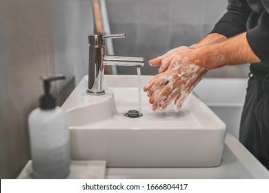 Washing hands with soap and hot water at home bathroom sink man cleansing hand hygiene for coronavirus outbreak prevention. Corona Virus pandemic protection by washing hands frequently.