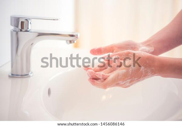 Hände mit Seife unter dem Wasserhahn waschen. Hygienekonzept.