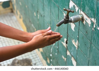Washing hands under flowing tap water at outdoor