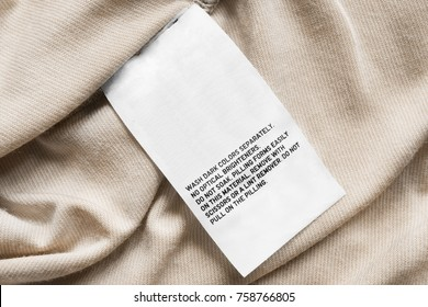 Washing instructions clothes label on beige textile background