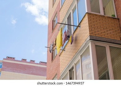 Washing and laundry drying on balcony of the apartment building on a sunny, hot summer day. Selective focus.