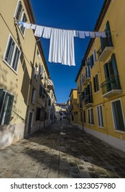 Washing line with laundry  hanging over the footpath on sunny day.Venice,Italy.