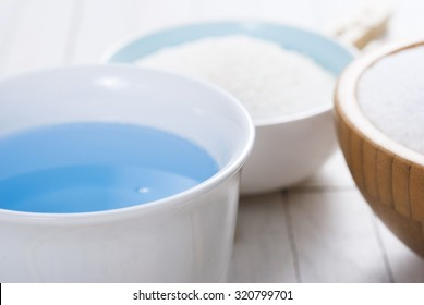 washing liquid and detergent powder with bamboo clothes pins on white wooden