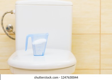 Washing machine detergent powder in containter standing bathroom on toilet. Housecare objects.