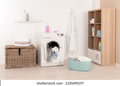 Washing machine with dirty clothes and towels in laundry room