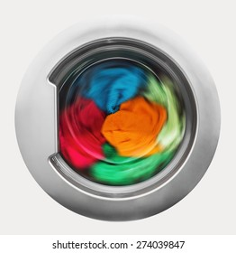 Washing machine door with rotating garments inside. focus in the center of dirty laundry and washing machine on the frame