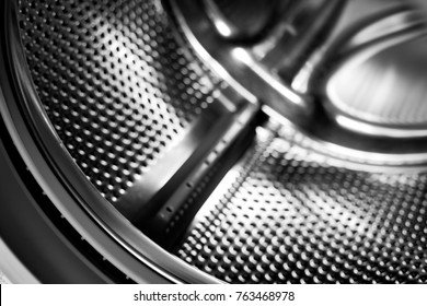 Washing machine drum interior. Perforated stainless steel drum for automatic washing machine. Black and white, metallic background