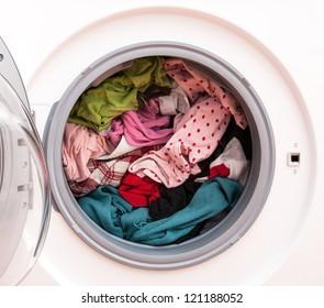 Washing machine full of dirty clothes, closeup