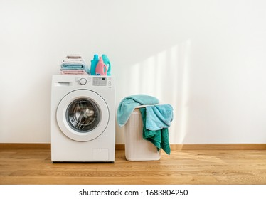 Washing machine, washing gels, clean towels and laundry baskets on white background