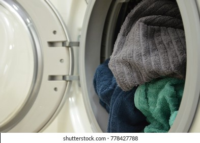 Washing machine with gray, blue, turquoise towels
