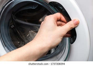 Washing machine. Hand opens washing machine lid. Do laundry concept