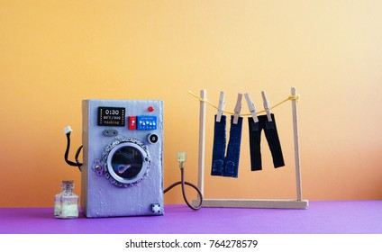 Washing machine with laundry, men's jeans pants dried on clothesline with clothespins. Yellow wall interior, violet floor. Funny toys creative design