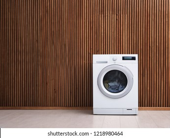 Washing machine with laundry near wooden wall. Space for text
