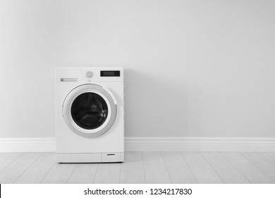 Washing machine near white wall, space for text. Laundry day
