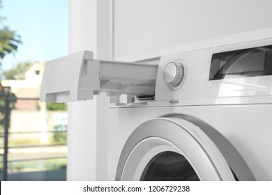 Washing machine with open detergent drawer in laundry room, closeup