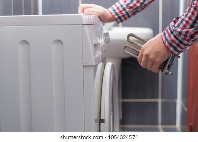 Washing machine repair. Repairer hands with defective heating element in front of damaged unit