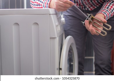 Washing machine repair. Repairer hands with screwdriver disassembling damaged unit of the heating element for repair