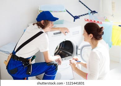 Washing machine repair service. Young technician examining and repairing tumble dryer. Woman looking at broken household appliance. Plumber with customer. Man fixing washer.