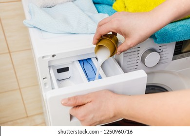 Washing powder detergent and measuring cup pouring into machine. Household duties, clothes laundry obejcts concept.