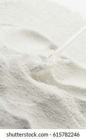 Washing powder with measuring spoon on background of washing powder.