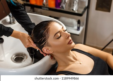 Washing procedure. Beautiful young woman with hairdresser washing head at hair salon.