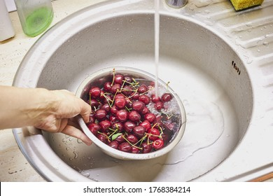 washing ripe cherry berries indoors domestik kitchen. water cleaning fruits. healthy eating and wellness concept. water splashes.
