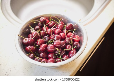 washing ripe cherry berries indoors domestik kitchen. water cleaning fruits. healthy eating and wellness concept.