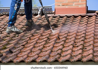 Washing the roof with a high pressure water washer.