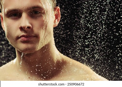 Washing stress away. Closeup portrait of young muscled man looking seriously through the water drops while taking a shower against black background