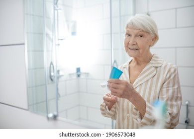 Washing up. Elderly woman doing morning procedures in the bathroom