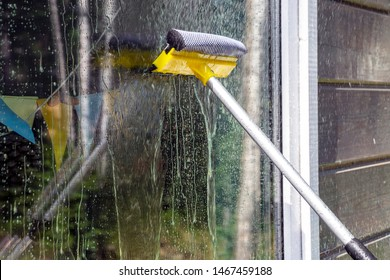 washing Windows, cleaning glasses and surfaces. yellow-white telescopic washing brush cleanly washes and wipes the Windows of the house.