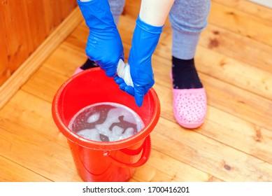 Parkettböden mit Gummihandschuhen waschen.