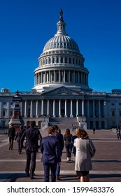 Washington DC—Dec 15, 2019; congressional members with lobbyists interns and staffers walk to the domed United States Capitol building in suits and business dress on a sunny day
