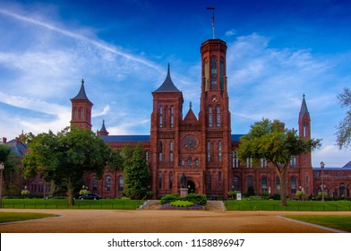 Washington DC—Aug 16, 2018; front entrance view of the red brick Smithsonian Institute Castle on the national mall with ornate gardens and statues in front.