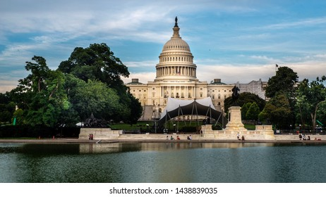 Washington DC—June 25th, 2019; stages and tents set up in front of United States Capitol building for Fourth of July concerts with reflection pond int he foreground.
