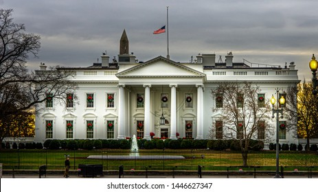 Washington DC—Dec 6, 2018; American flag at half mast over the White House Presidential Residence at sunrise with Christmas Holiday Decorations and wreaths hanging on the outside.