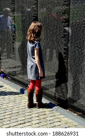 Washington, DC - April 10, 2014:  A little girl studies names inscribed on the black granite wall of the Vietnam War Memorial on the National Mall