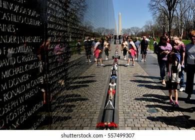 Washington, DC - April 10, 2014:  Visitors viewing the black granite wall inscribed with fallen soldier's names at the Vietnam War Memorial on the National Mall