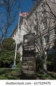WASHINGTON, DC - APRIL 2017: The Internal Revenue Service - IRS - headquarters in building and sign, wide shot. American flag above on Constitution Ave. Signage is new in 2017. Washington DC.