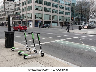 WASHINGTON, DC - APRIL 2018: LimeBike dockless electric scooters downtown.(note rider on street) One of several dockless bike companies in DC; introduced dockless electric scooters in March 2018,