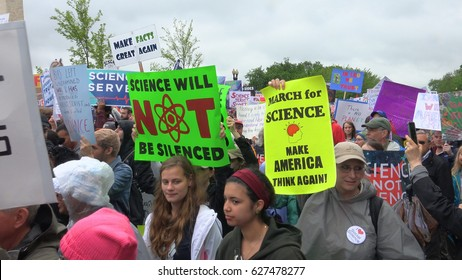 """WASHINGTON, DC - APRIL 22, 2017: """"Make America Think Again""""  among may placards in March for Science on Constitution Ave. on a rainy Earth Day 2017."""