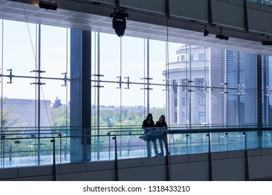 Washington, DC - April 26, 2014: Interior of Newseum with silhouette of 2 visitors in front of windows